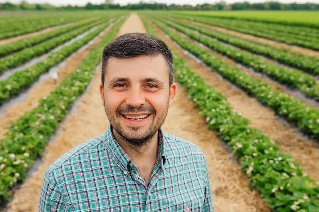 Portret młodego kaukaskiego przystojnego szczęśliwego rolnika stojącego w polu truskawkowym i uśmiechającego się do kamery młodego zadowolonego rolnika stojącego przed gruntami rolnymi