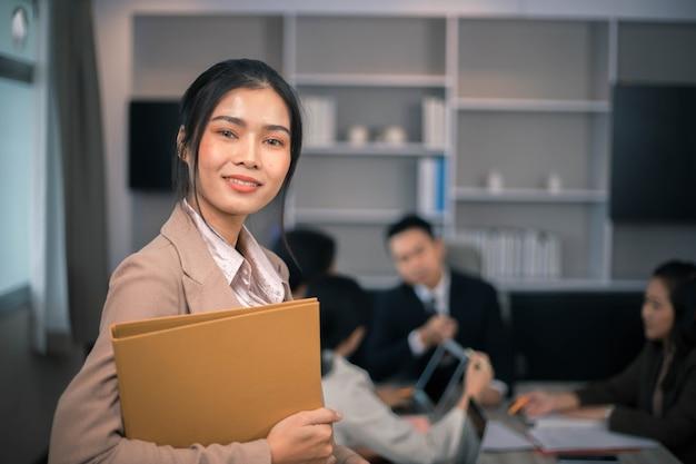 Portret młodego kierownika biura pewnie kobiet w jej miejscu pracy, gotowy do wykonywania zadań biznesowych.