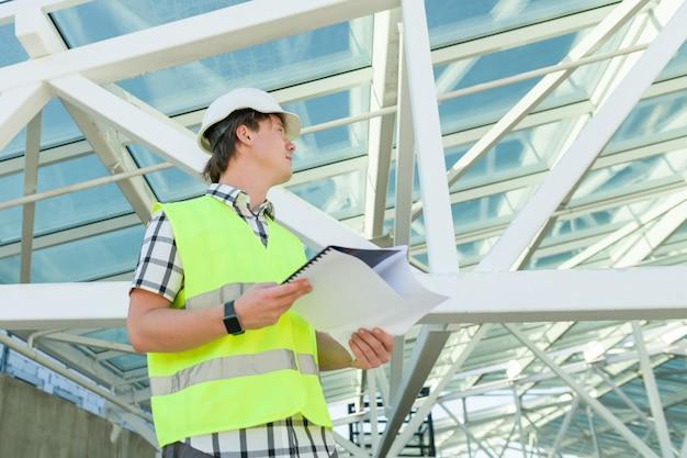 Portret młodego konstruktora płci męskiej na budowie
