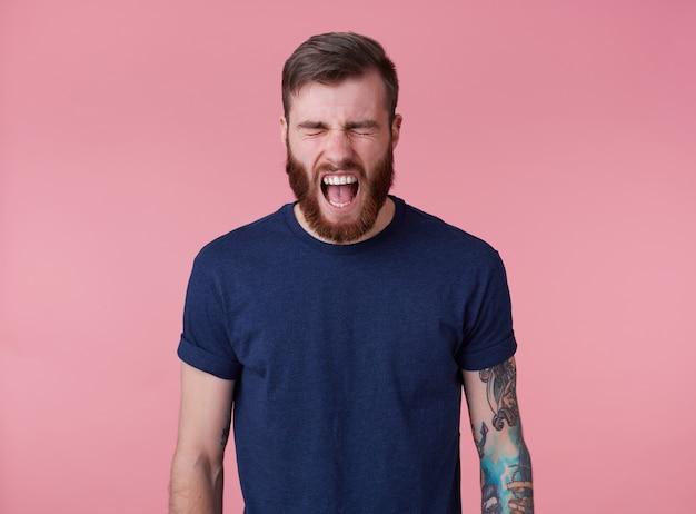 Portret młodego krzyczącego, wytatuowanego mężczyzny z czerwoną brodą w pustej koszulce, odczuwa silny ból i złość, stoi na różowym tle z zamkniętymi oczami i szeroko otwartymi ustami.