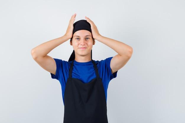 Portret młodego kucharza z rękami na głowie w koszulce, fartuchu i patrząc wesoły widok z przodu