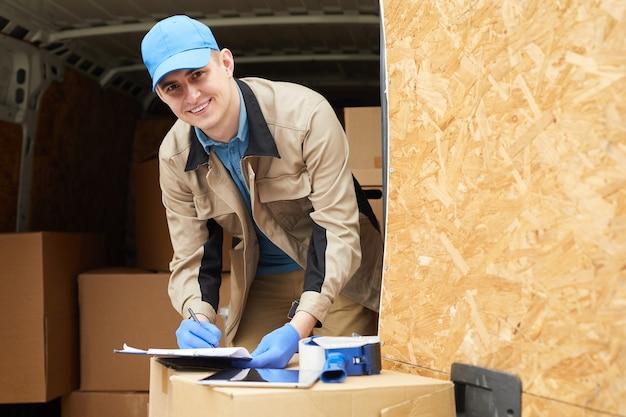 Portret młodego kuriera uśmiecha się do kamery podczas wypełniania dokumentu, który dokonuje dostawy ładunku