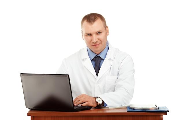 Portret młodego lekarza płci męskiej w białym fartuchu na białym