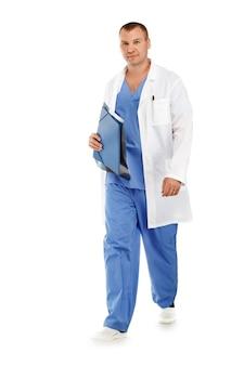 Portret młodego lekarza płci męskiej w niebieskim mundurze medycznym chirurgicznym w ruchu opuszczającym salę operacyjną na białym