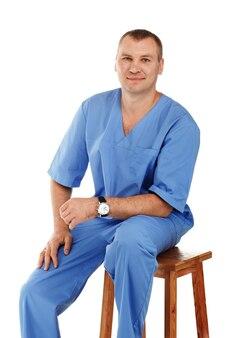 Portret młodego lekarza płci męskiej w odzieży medycznej chirurgicznej lub laboratorium niebieski na białym