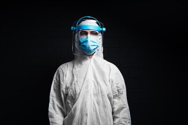 Portret młodego lekarza w kombinezonie ppe przeciwko koronawirusowi i covid-19