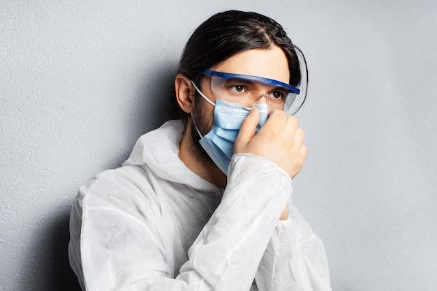 Portret młodego lekarza w kombinezonie ppe, zakładającego medyczną maskę na twarz przeciwko koronawirusowi i covid-19.