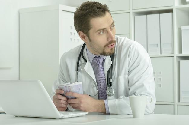 Portret młodego lekarza z laptopem i pieniędzmi