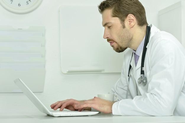 Portret młodego lekarza z laptopem