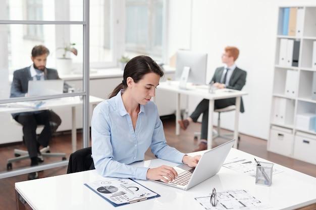 Portret młodego los za pomocą laptopa siedzącego przy biurku w biurze, kopia przestrzeń