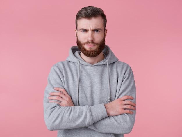 Portret młodego marszczącego brwi przystojnego, rudego brodacza w szarej bluzie z kapturem, stoi ze skrzyżowanymi rękami, z dezaprobatą patrzy na aparat, stoi na różowym tle.