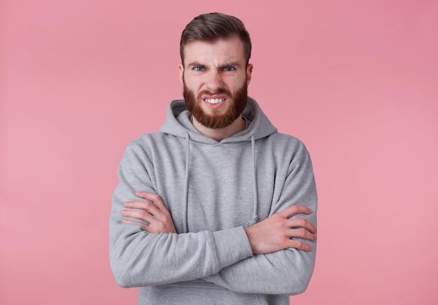 Portret młodego, marszczącego brwi, przystojnego, rudego brodatego mężczyzny w szarej bluzie z kapturem, stoi ze skrzyżowanymi rękami, złe spojrzenie na aparat, obnaża zęby, stoi na różowym tle.