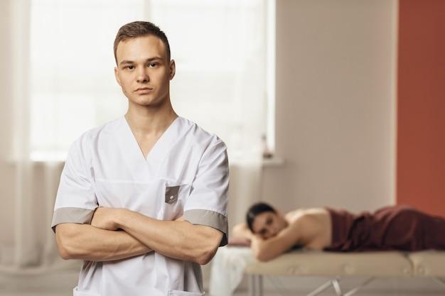 Portret młodego masażysty pozującego w jego biurze