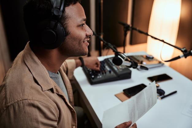 Portret młodego męskiego prezentera radiowego nadawanego na żywo, rozmawiającego przez mikrofon, trzymającego papier ze scenariuszem