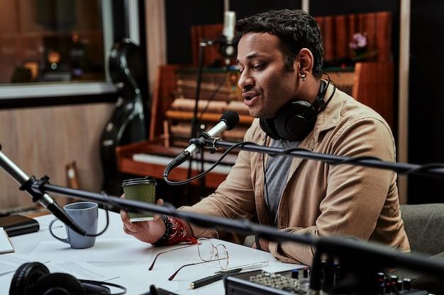 Portret młodego męskiego prezentera radiowego pijącego drinka, który wygląda na skupionego podczas mówienia do mikrofonu