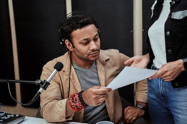 Portret młodego męskiego prezentera radiowego wyglądającego poważnie podczas odbierania, trzymając papier ze skryptem, który dostaje