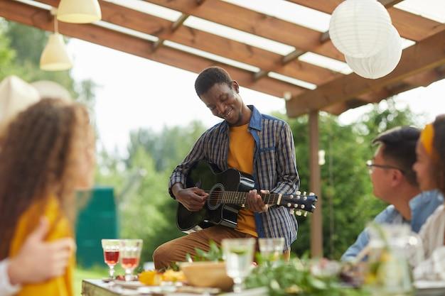 Portret młodego mężczyzny african-american gry na gitarze, stojąc przy stole i delektując się kolacją z przyjaciółmi na świeżym powietrzu na summer party