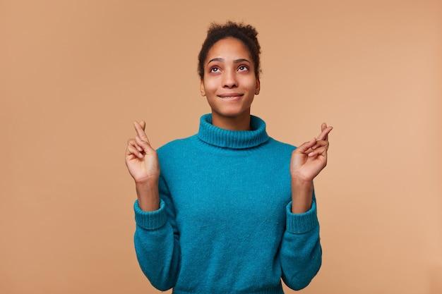 Portret młodego mężczyzny african american ubrany w niebieski sweter z kręconymi ciemnymi włosami. patrzy w górę, przygryza wargę, trzyma kciuki i składa życzenie. pojedynczo na beżowym tle.