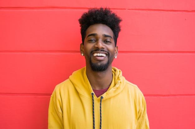 Portret młodego mężczyzny afro amerykanina patrząc pewnie i pozowanie przed czerwoną ścianą.