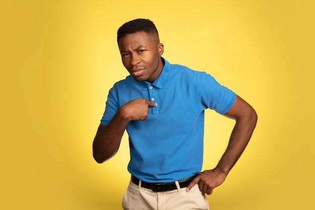 Portret młodego mężczyzny afro-amerykańskiego na białym tle na żółty, wyraz twarzy.