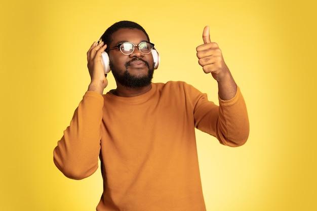 Portret młodego mężczyzny afro-amerykańskiego na białym tle na żółtym tle studio, wyraz twarzy.