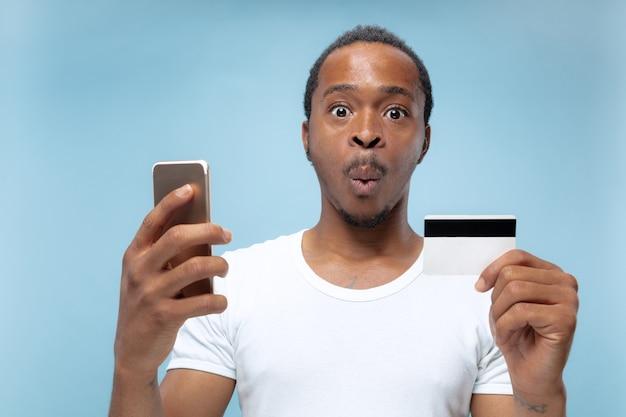 Portret młodego mężczyzny afro-amerykańskiego w białej koszuli, trzymając kartę i smartfon.