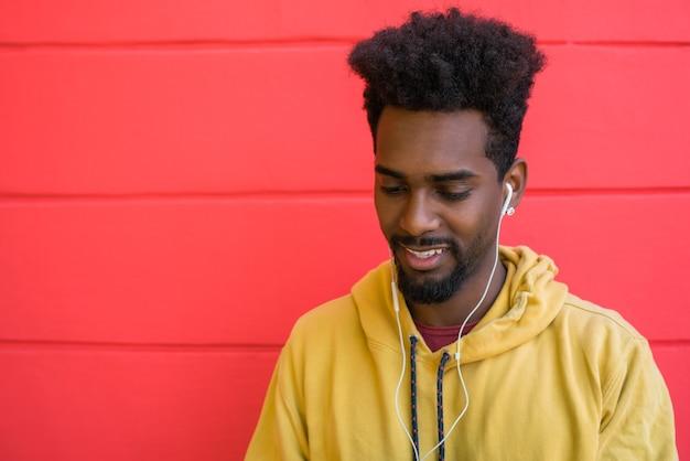 Portret młodego mężczyzny afro, ciesząc się i słuchając muzyki przez słuchawki. koncepcja technologii i stylu życia.