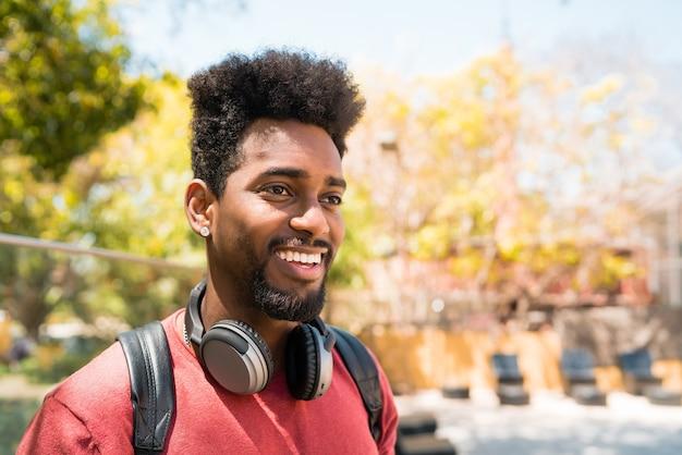 Portret młodego mężczyzny afro, ciesząc się i słuchając muzyki w słuchawkach. koncepcja technologii i stylu życia.