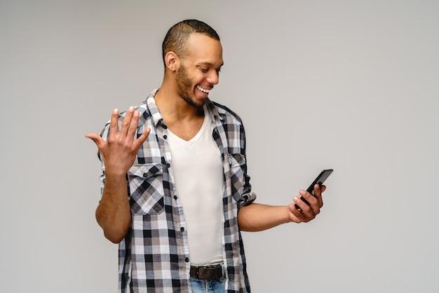 Portret młodego mężczyzny afroamerykanów posiadających telefon komórkowy.