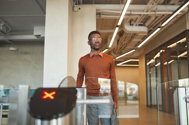 Portret młodego mężczyzny afroamerykanów, przesuwając samochód id podczas przechodzenia przez automatyczną bramę, aby wejść do budynku biurowego lub uczelni, miejsce na kopię