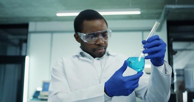 Portret młodego mężczyzny afroamerykanów w okularach i białej szacie robi analizę niebieskiego płynu w probówce podczas badań medycznych lub farmaceutycznych w laboratorium.