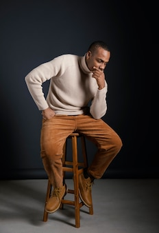 Portret młodego mężczyzny afrykańskiego siedzi na krześle