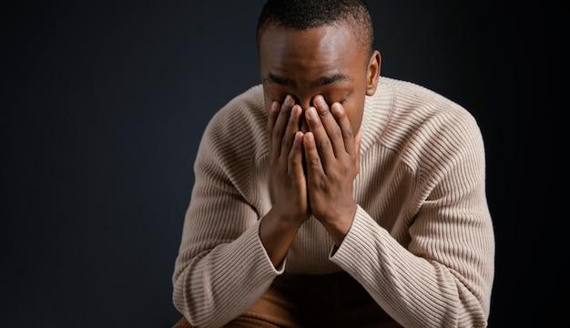 Portret młodego mężczyzny afrykańskiego z rękami zakrywającymi twarz