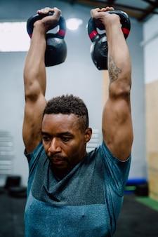 Portret młodego mężczyzny atletycznego robi ćwiczenia z kettlebel crossfit na siłowni. crossfit, sport i koncepcja zdrowego stylu życia.