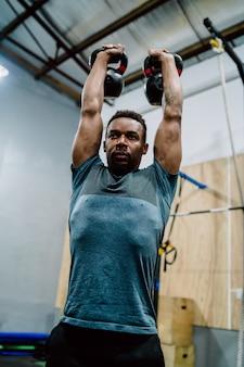 Portret młodego mężczyzny atletycznego robi ćwiczenia z kettlebel crossfit na siłowni