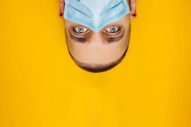 Portret młodego mężczyzny atrakcyjnego przewrócił oczami w masce ochronnej na twarzy. strach przed zachorowaniem, koncepcja koronawirusa. bez źrenic. patrzy od góry do dołu.