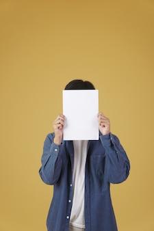 Portret młodego mężczyzny azjatyckiego ubrany niedbale pokazując puste puste afisz papier na białym tle.