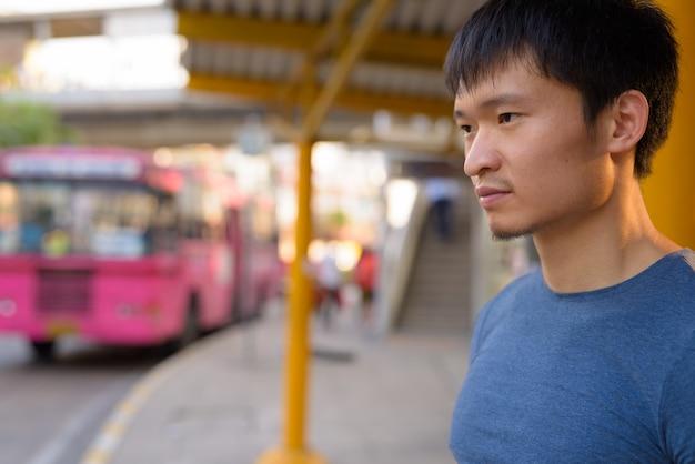 Portret młodego mężczyzny azji na przystanku autobusowym
