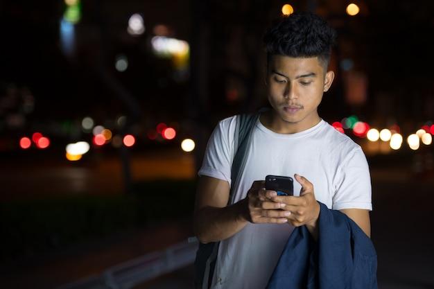 Portret młodego mężczyzny azji na ulicy miasta w nocy na zewnątrz