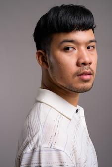 Portret młodego mężczyzny azji przeciwko szarości