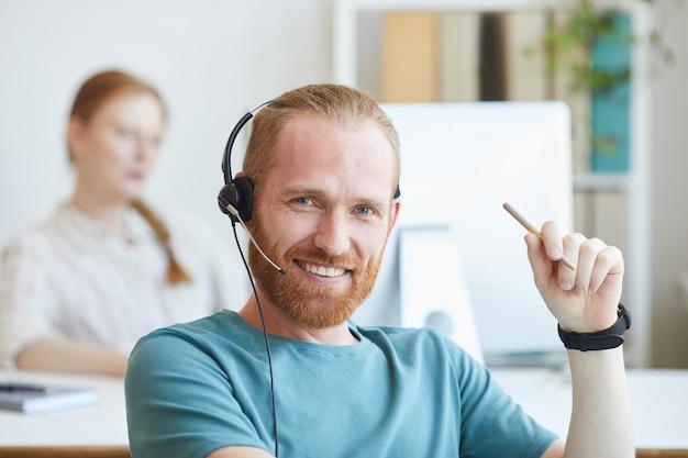 Portret młodego mężczyzny brodaty w zestaw słuchawkowy uśmiecha się podczas pracy w biurze