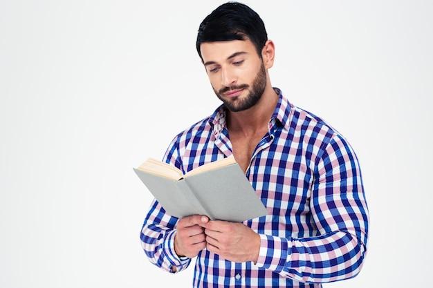 Portret młodego mężczyzny, czytanie książki na białym tle na białej ścianie