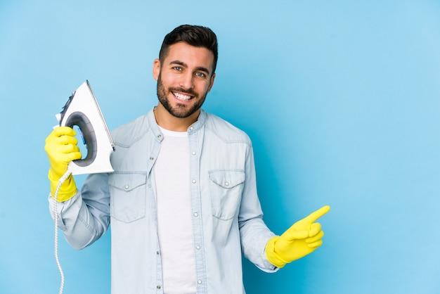 Portret młodego mężczyzny do prasowania na białym tle, uśmiechając się i wskazując na bok, pokazując coś w pustym miejscu.