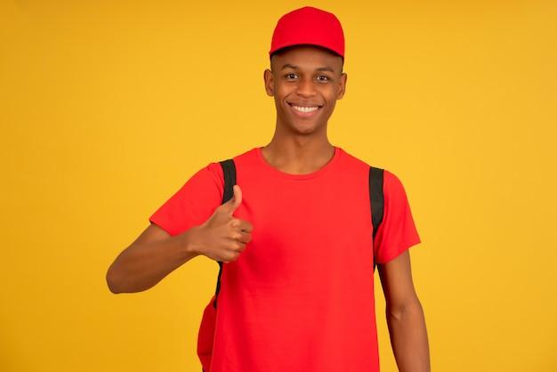 Portret młodego mężczyzny dostawy patrząc w kamerę i pokazując kciuk do góry stojąc na odosobnionym żółtym tle. koncepcja usługi dostawy.