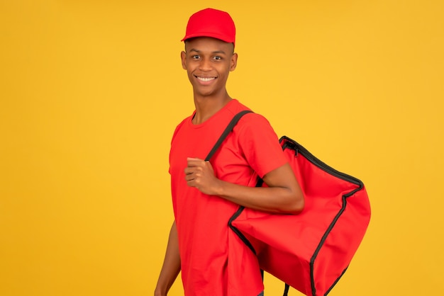Portret młodego mężczyzny dostawy patrząc w kamerę stojąc na białym tle żółty. koncepcja usługi dostawy.