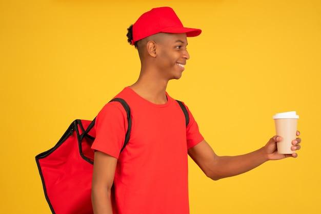 Portret młodego mężczyzny dostawy trzymając filiżankę kawy na wynos. koncepcja usługi dostawy.