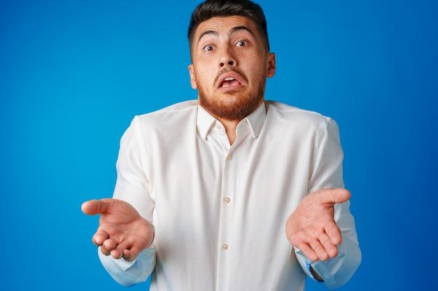 Portret młodego mężczyzny frajera wzruszając ramionami, nie wiem, gest z bliska