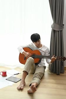 Portret młodego mężczyzny gra na gitarze akustycznej na podłodze w salonie.