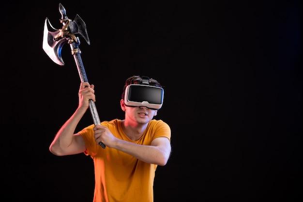 Portret młodego mężczyzny grającego w vr z toporem bojowym na ciemnej ścianie