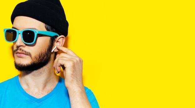 Portret młodego mężczyzny hipster w niebieskiej koszuli, ubrany w błękitne okulary przeciwsłoneczne i czarną czapkę